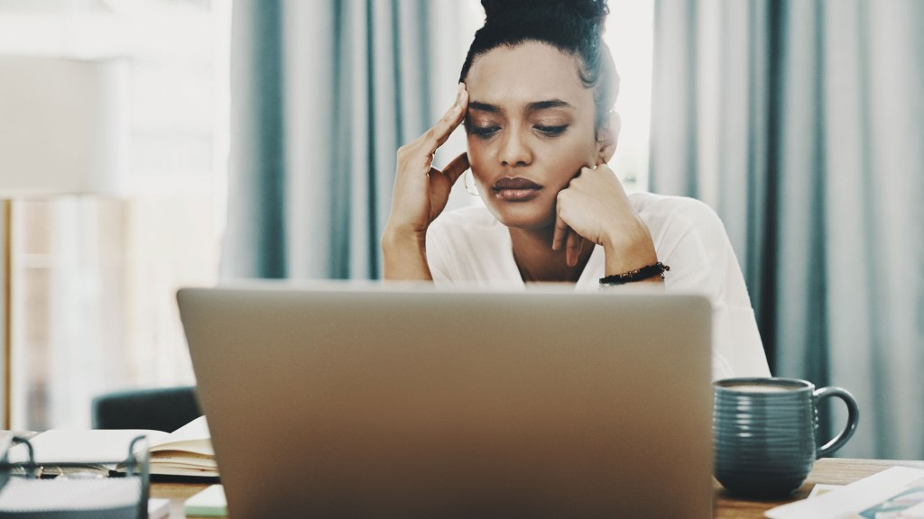 Woman looking at laptop with hand on her forehead in a stressed fashion.